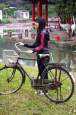 Asian woman riding bicycle with smile — Stock Photo