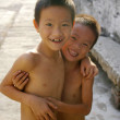 Two young Chinese boys smiling in a village — Stock Photo