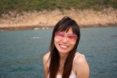 Asian woman smiling with sunglasses in summer — Stock Photo