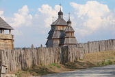 Wooden stockade and a church — Stock Photo