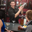 Bartender shaking cocktail friends having drink — Stock Photo #10118670