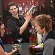 Stock Photo: Bartender shaking cocktail friends having drink