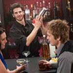 Bartender shaking cocktail friends having drink — Stock Photo