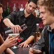 Bartender shaking cocktail friends having drink — Stock Photo