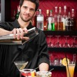 Young bartender make cocktail shaking drinks - Stock Photo