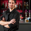 Barman in black standing at cocktail bar — Stock Photo #10118757