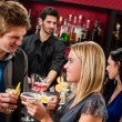 Happy friends at cocktail bar enjoy drinks — Stock Photo