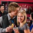 Flirting happy friends drinks at cocktail bar — Stock Photo