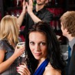 Attractive girl smiling with friends at bar - Stock Photo