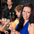 Party girl smiling with friends at bar — Stock Photo #10118809