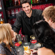 Stock Photo: Barman chatting with friends drinking at bar