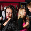 Attractive girl smiling with friends at bar — Stock Photo