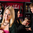 Attractive girl at bar smiling with friends — Stock Photo
