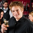 Young man at the bar drink champagne — Stock Photo