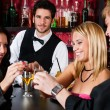 Stock Photo: Barman behind counter friends drinking at bar