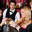 Barman behind counter friends drinking at bar — Stock Photo #10118872