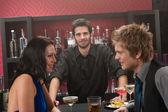 Bartender behind the bar friends having drink — Stock Photo