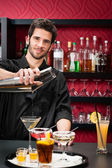 Young bartender make cocktail shaking drinks — Stock Photo