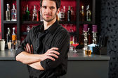 Barman in black standing at cocktail bar — Stock Photo