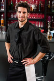 Professional barman in black standing bar — Stock Photo