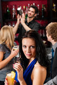 Attractive girl smiling with friends at bar — Foto de Stock