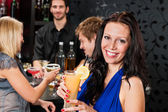 Party girl smiling with friends at bar — Stock Photo
