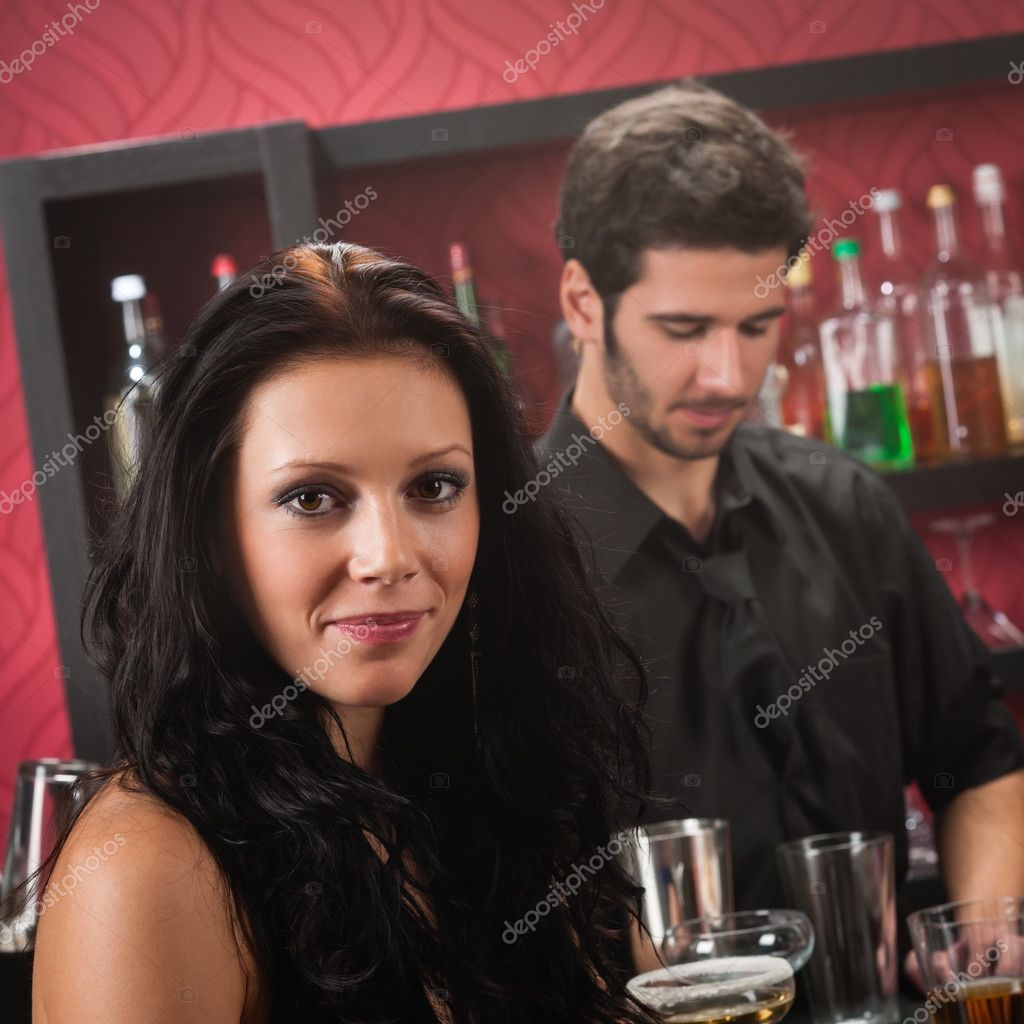 Beautiful young brunette woman having drink at the bar — Stock Photo #10118652