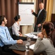 Business man at team meeting point flip-chart — Stock Photo