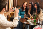 Friends at the bar man take picture — Stock Photo