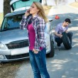 Woman calling for car assistance change wheel — ストック写真