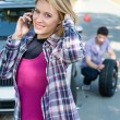 Woman calling for car assistance change wheel — Stock Photo