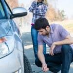 汽车车轮缺陷的男人改变穿刺轮胎 — 图库照片