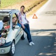 Stock Photo: Car defect man helping two female friends