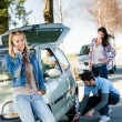 Broken wheel man helping two female friends - Stock Photo