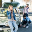 Foto de Stock  : Wheel defect mhelping two female friends