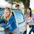 Pushing car technical failure young friends road — Stock Photo