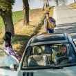 Hitch-hiking parked car girl friends offer lift - Stock Photo
