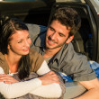 Camping young couple lying car summer sunset — Stock Photo