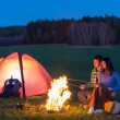 Tent camping car couple sitting by bonfire — Stock Photo #10235449