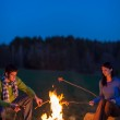 Couple cook by bonfire romantic night countryside — Stock Photo #10235486