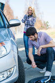 Car wheel defect man change puncture tire — ストック写真
