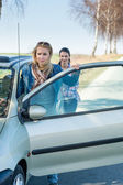 Pushing car technical failure two young women — Foto Stock