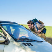 Hitch-hiking getting lift young woman in car — Stock Photo