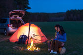 Tent camping car couple sitting by bonfire — Stok fotoğraf