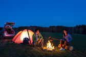Tent camping car couple sitting by bonfire — Stockfoto