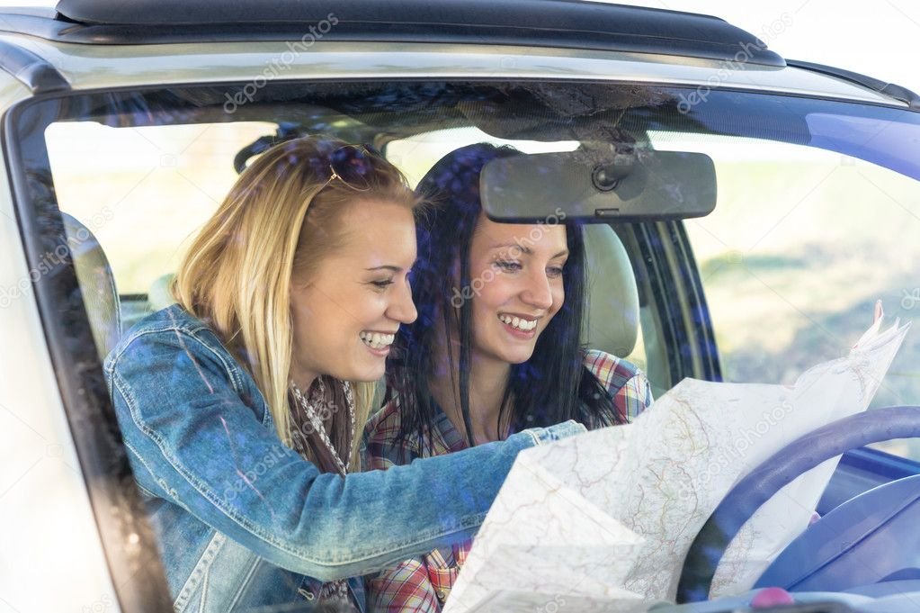Lost with map two young friends in car enjoy road trip — Stock Photo #10234941