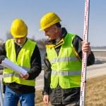 Geodesist two man theodolite stand highway — Stock Photo