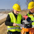 Geodesist two man theodolite stand highway - Stock Photo