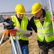 Geodesist two man theodolite stand highway — Stock Photo
