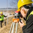 Stock Photo: Geodesist measure land with tacheometer highway
